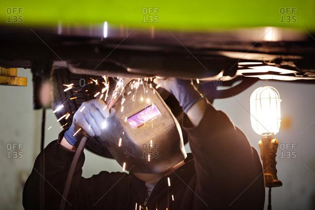 A man welding underneath a car