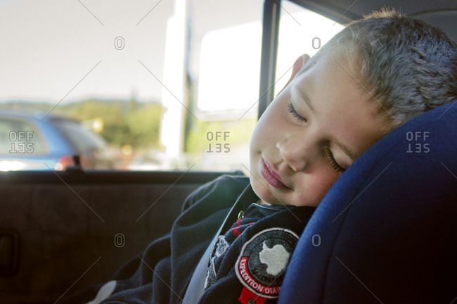 Young boy taking nap in car seat