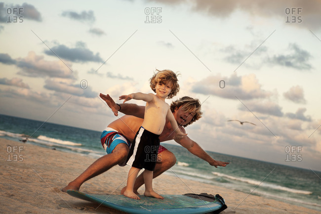 Dad teaching son how to surf