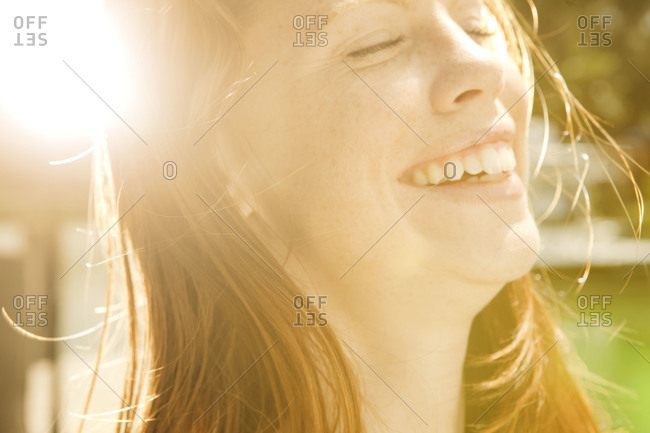 Woman smiles with eyes closed