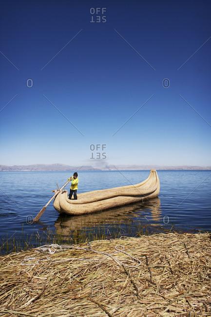 Young boy on handmade canoe