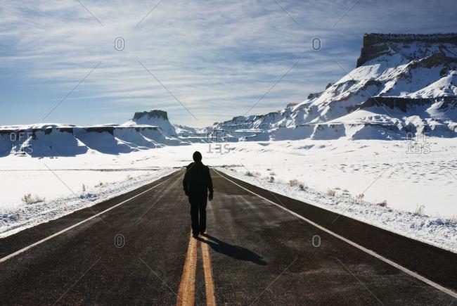 Man walking deserted highway in Utah