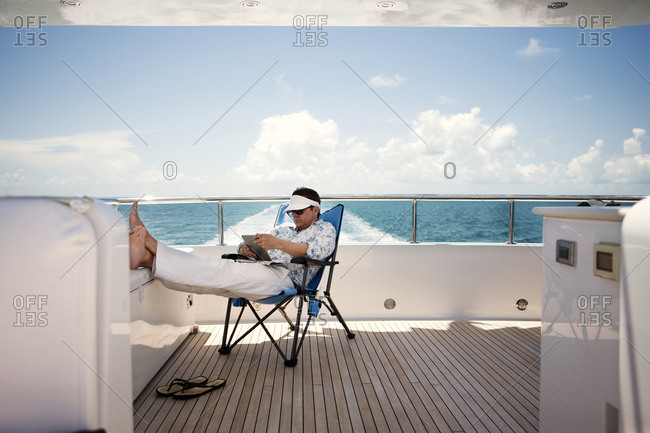 A man with a tablet on a yacht