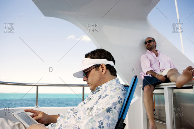 Two men lounge on the deck of a yacht