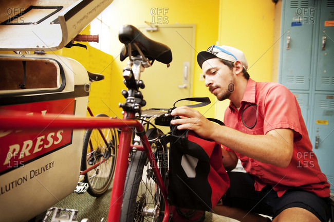 A young man attaches a bag to a bicycle