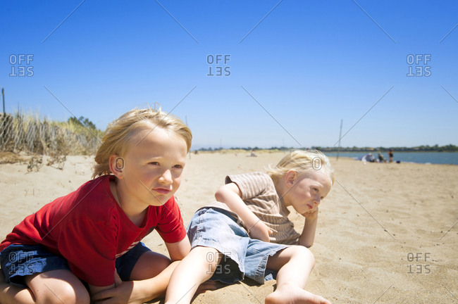Two boys laying on the beach