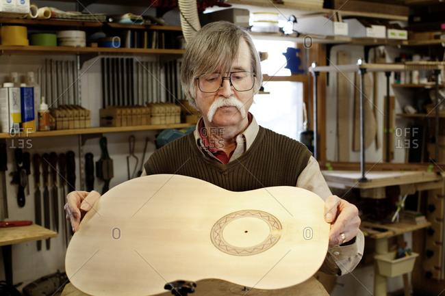 Older man holding outline of guitar
