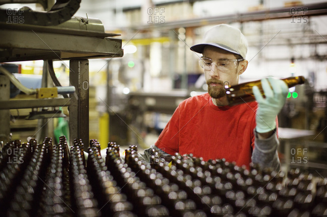 Brewery worker with beer bottles