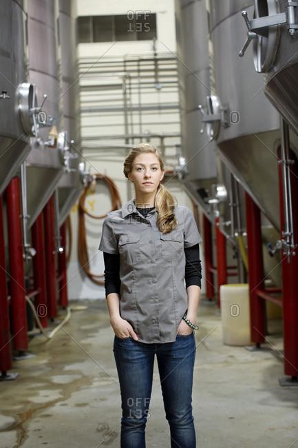 Portrait of brewery worker with beer vats