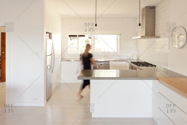 Woman walking through contemporary kitchen