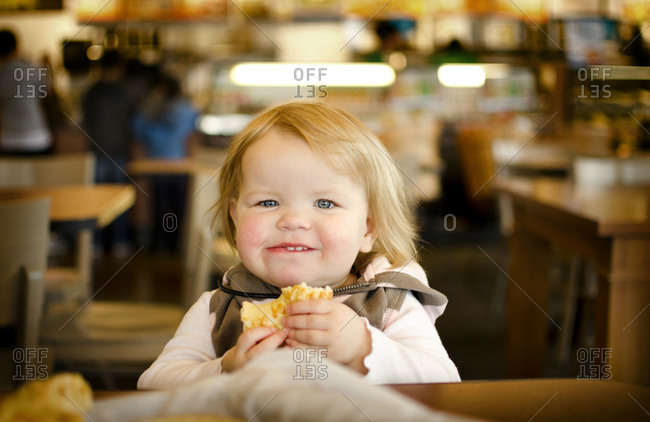A little girl eating in a food court