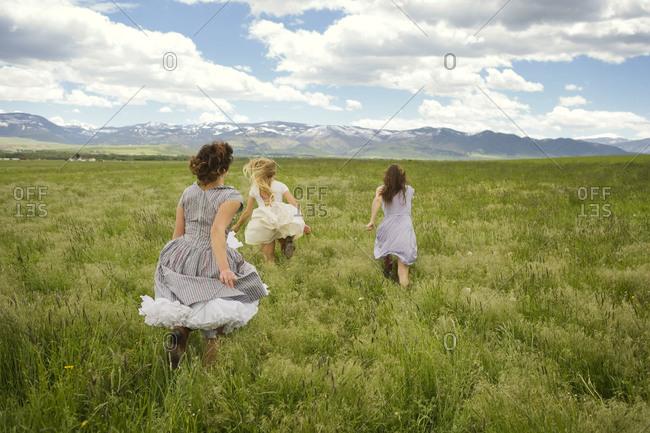Three women run through a field
