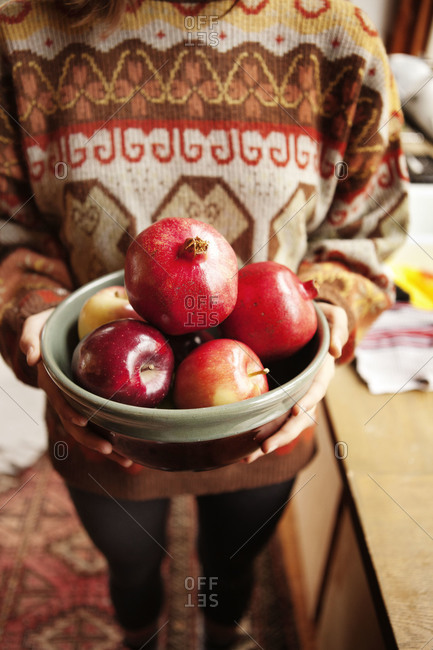 A woman holds a bowl of pomegranate and apples