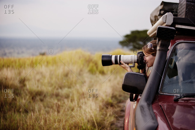 A woman using a telephoto lens in Queen Elisabeth National Park