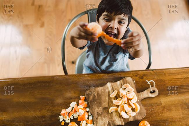 Boy peeling oranges and being goofy