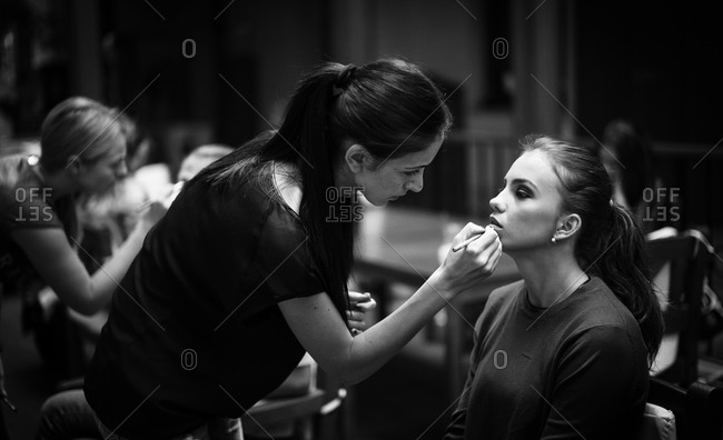 Sibiu, Transylvania, Romania - September 5, 2014: Woman applying lipstick to runway model