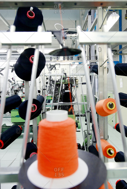 Spools of thread strung up on an industrial sewing machine