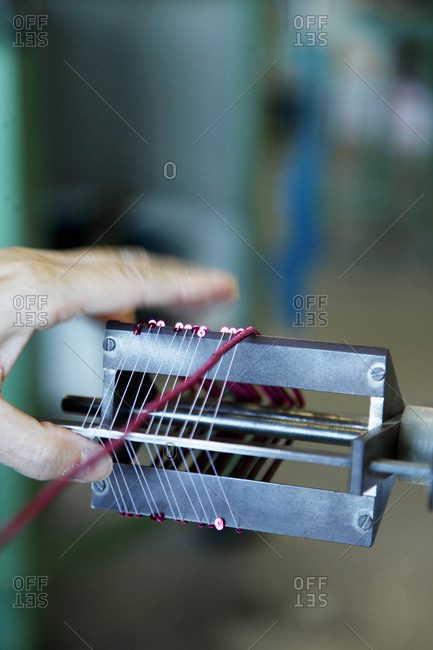 A woman strings together rows of sequins at a sequin manufacturing company in Milan, Italy