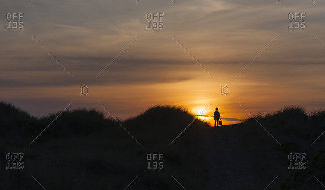 Girl in dune at sunset