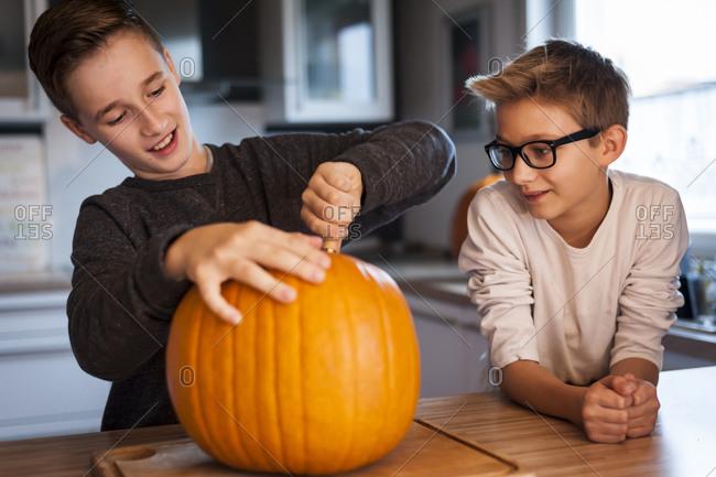 Two boys preparing a big pumpkin for Halloween lantern