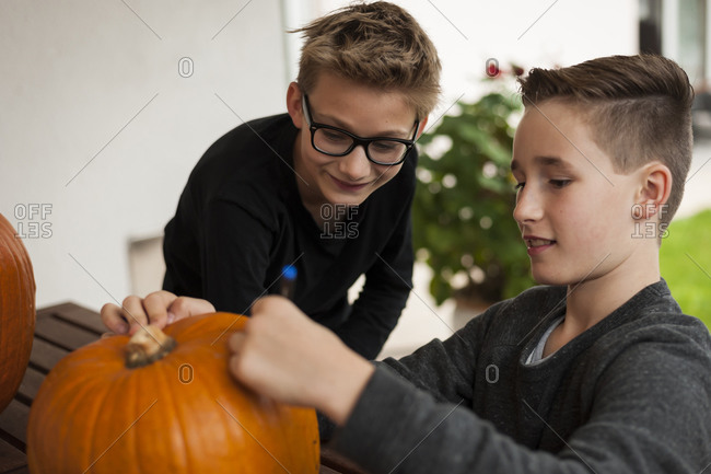 Two boys preparing a pumpkin for Halloween lantern