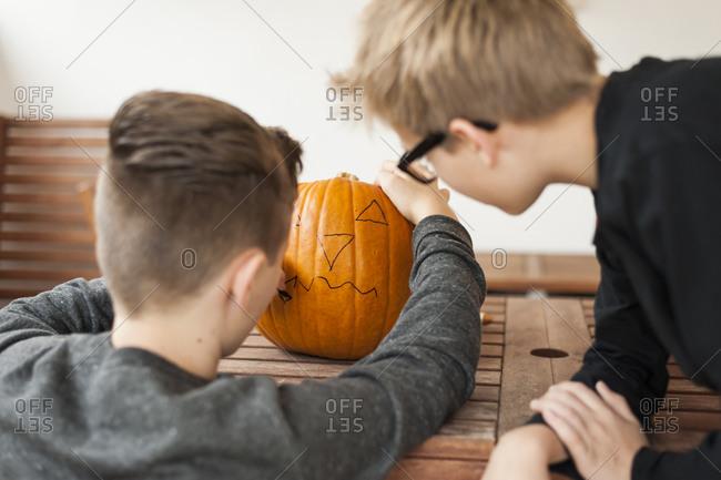 Two boys preparing a pumpkin for Halloween lantern