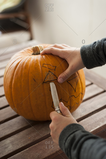 Boy\'s hands preparing a pumpkin for Halloween lantern