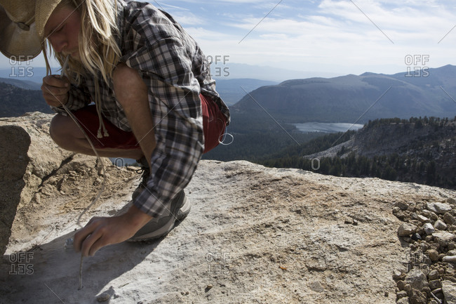 Professional highliner using a plastic tube to blow the rock dust out of recently drilled holes while bolting and establishing a highline on top of Mammoth Crest