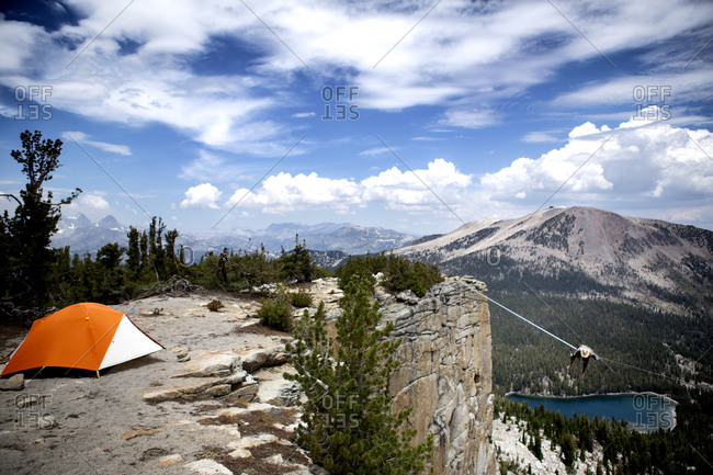 Male highliner pitches a tent next to a 125 foot highline rigged over a lake in a gap on top of Mammoth Crest