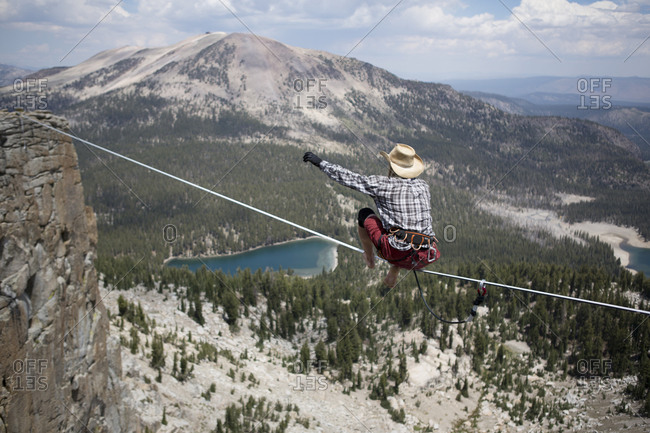 Male highliner in cowboy hat stands up on a 125 foot highline over a lake in a gap on top of Mammoth Crest