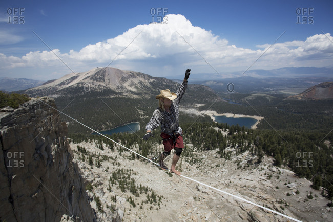 Male highliner in cowboy hat walks a 125 foot highline over lakes in a gap on top of Mammoth Crest