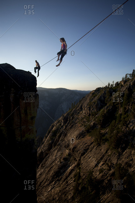 Female highliners simultaneously sitting on a highline above the Yosemite Valley floor at Taft Point