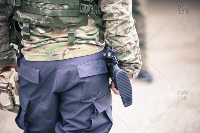 A man in camo gear carries a gun and goggles