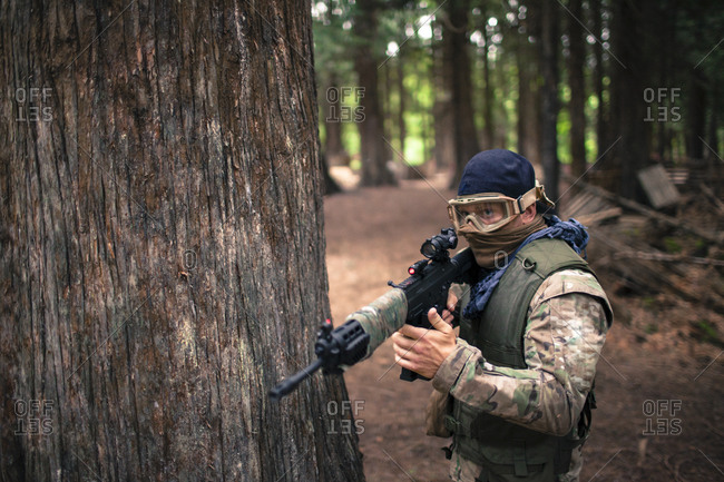 A man carries an automatic weapon while walking through the forest