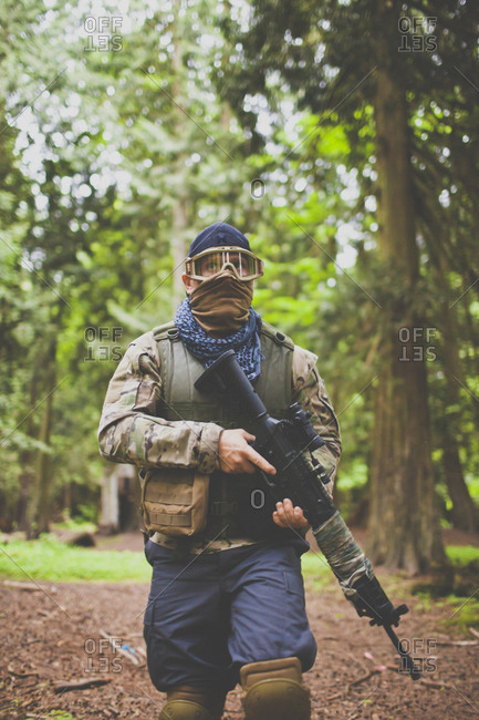 Man carrying automatic weapon through the forest