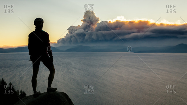A mountain biker stops on the Flume Trail to watch smoke from a wildfire