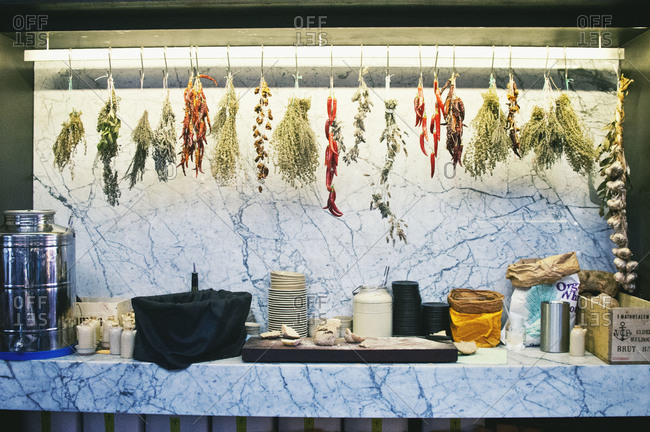 Herbs drying on hooks above kitchen supplies