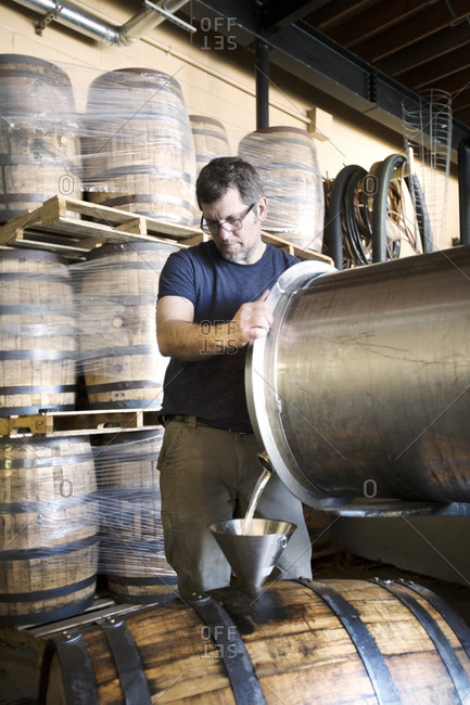 A brewer decanting whiskey into oak barrels