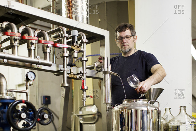 A brewer sampling whiskey at a distillery