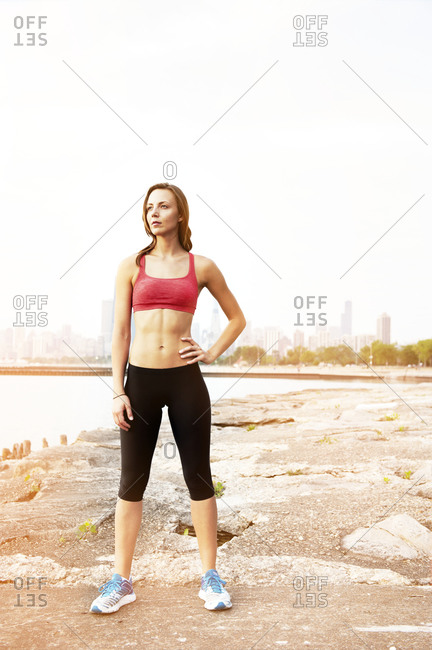 A woman in workout gear stands in front of the Chicago skyline