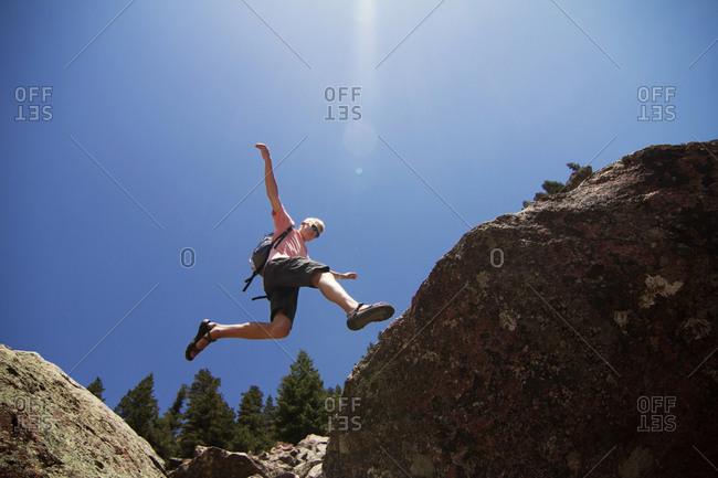 A man jump over a crevice