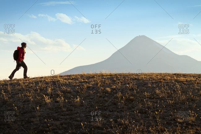 A woman hiking across barren terrain