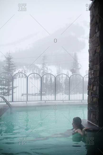 A woman in a heated pool in the winter