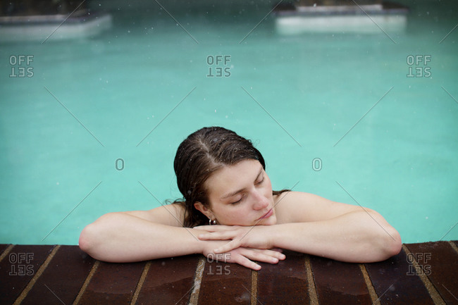 A woman laying on the edge of a heated pool