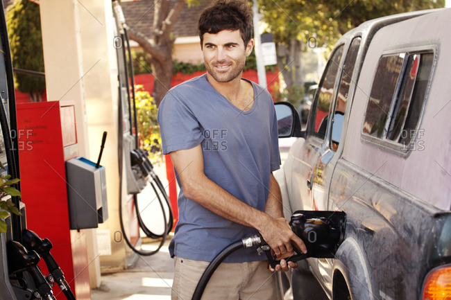 A man pumps gas at a gas station