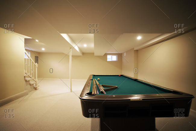 A pool table in an empty basement
