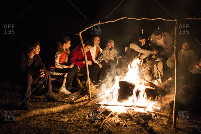 A group of people gather around a fire