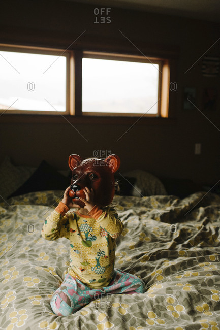 Child sitting on bed wearing bear mask