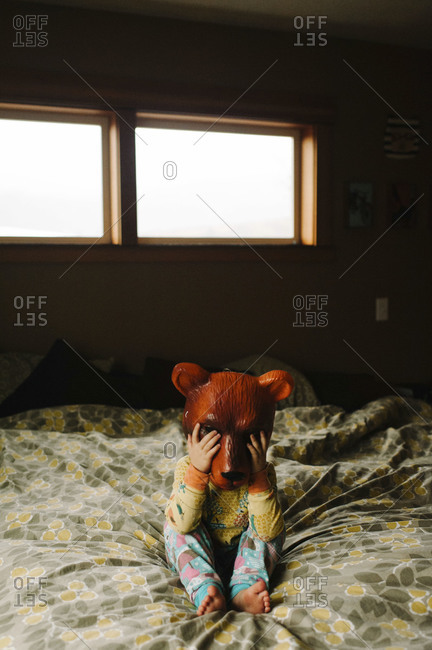 Child on bed wearing bear mask