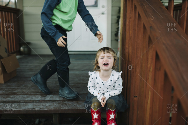 Girl crying on porch steps with brother